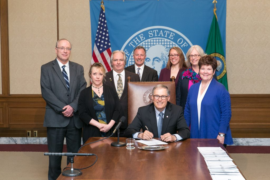 Governor Jay Inslee signs Substitute Senate Bill No. 5597, March 31, 2016. Relating to real estate appraisers. Shown from left to right. Jerry McDonald, Administrator, Real Estate Programs; Dee Sharp, Appraisers Program Manager; Bob Mossuto, MNAA, ACOW Board Member;T.K. Bentler, ACOW Lobbyist; Stephanie Sams, Policy and Legislative Analyst, Director's Office; Kathleen Drew, Assistant Director for Business and Professional Licensing; Senator Pam Roach, President Pro Tempore and Chair of the Senate Government Operations and Security. Seatedd in front is Governor Jay Inslee.
